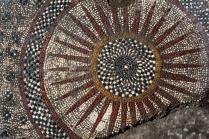 L'un des deux motifs centraux du pavement mosaïqué, composé de couronnes, rayons et damiers.
